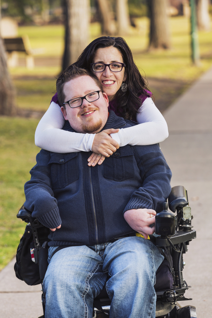 Disabled husband with his wife posing for a picture in a park.