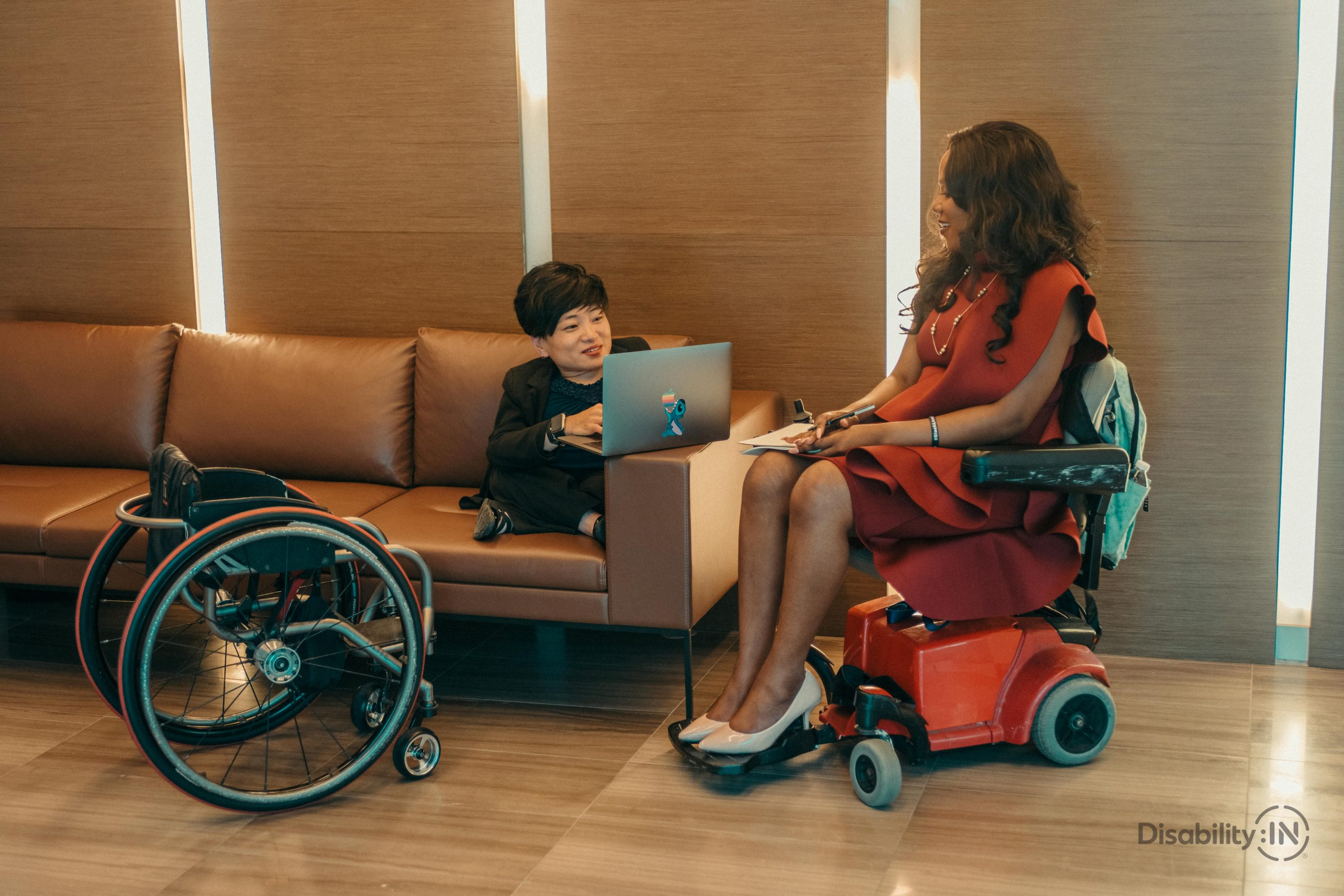 two disabled women colleagues in wheelchair